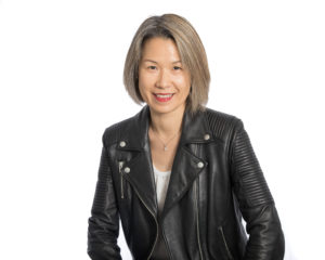 Headshot of Addy who is a woman wearing black leather jacket is smiling at the camera.