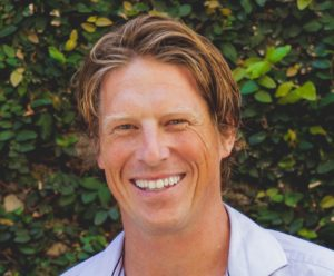 Headshot of Ben, who is a man smiling while outdoors in front of greenery.