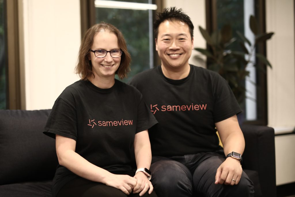 A woman and a man wearing t-shirts with the words sameview sitting on a grey sofa smiling at the camera