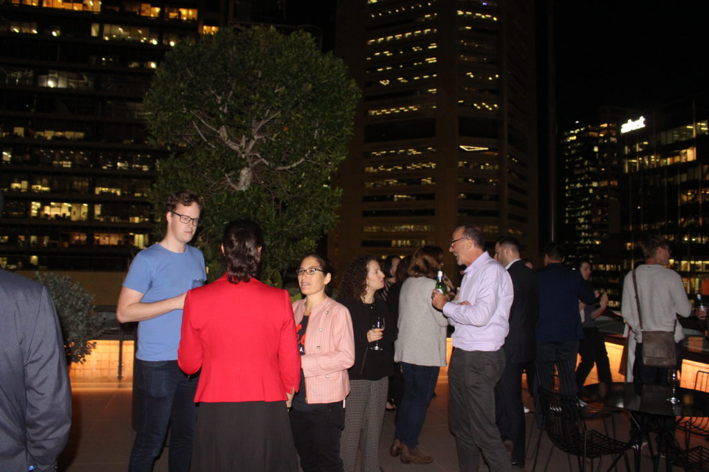 A group of people on a rooftop building at night networking.