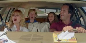 A family driving and singing in a car.