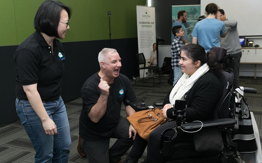 2 Remarkable Founders from Spokle speak to a customer who is a wheelchair user in the foreground. All three are laughing or smiling. While a group of five people mingle in the background.