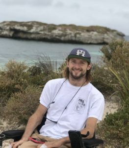Steve Ralph is in a white tee shirt and navy cap seated in his wheelchair, while smiling to the camera at the beach.