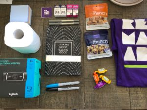 A care package laid out on a carpet floor including toilet paper, webcam, sharpies, a Remarkable t-shirt, notepad, almond snacks and stickers.