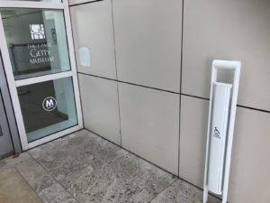 A glass door and the white accessible door opening button that is a long bar that stretches from close to the floor to around 1m off the ground.