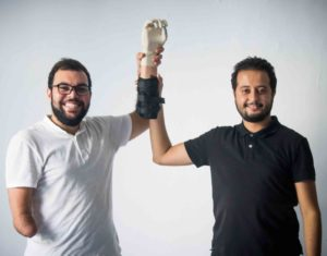 Two men standing in a studio setting both holding a bionic arm prototype.