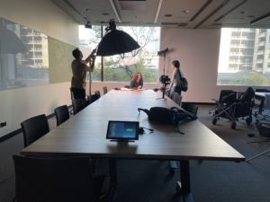 Lady seated behind a boardroom table with a camera operator and producer in front of her.