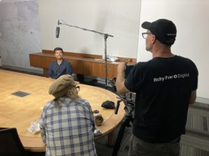 Young man seated at a long board room table with a microphone positioned on top of his head and two producers positioned behind a camera.