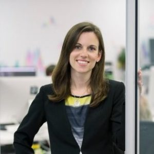 Headshot of Agi, who is a woman standing in an office setting wearing corporate clothing and smiling at the camera.